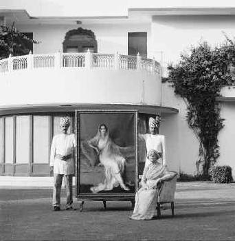 he Rajmata Gayatri Devi Sahiba seated on the right. Behind her are two courtiers holding up a magnificent portrait of her mother the most beautiful Maharani Indira Devi of Cooch-Behar. This picture was taken on the lawns of the Lillypool. Lillypool is the Rajmata's home on the grounds of Rambagh Palace, Jaipur.
