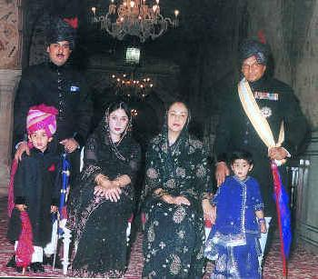 This is the current royal family of Jaipur. Standing on the right with a white sash is His Highness Brigadier Maharaja Sawai Bhawani Singh. In front of the Maharaja in the blue dress is his granddaughter. Seated next to her is Her Highness Maharani Padmini Devi. The Princess Diya Kumari is seated next to the Maharani, and standing on the left is the princess's husband Mr. Narendra Singh. Finally the heir to the Jaipur Gaddi, Maharaj Kumar Padmanabh Singh is standing in the prink turban. He is the son of Princess Diya Kumari and Mr. Narendra Singh, and was recently adopted by Maharaja Bhawani Singh accompanied by a stately ceremony as the heir to the Jaipur Gaddi.