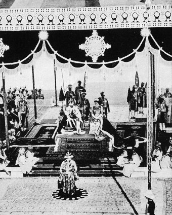 Their Imperial Majesties the Emperor George V and Empress Mary seated on the imperial thrones while they receive allegience from five hundred plus Princes of Royal India.