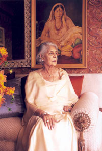Her Highness Rajmata Gayatri Devi Sahiba.  The Rajmata poses for the camera in a gold evening gown.